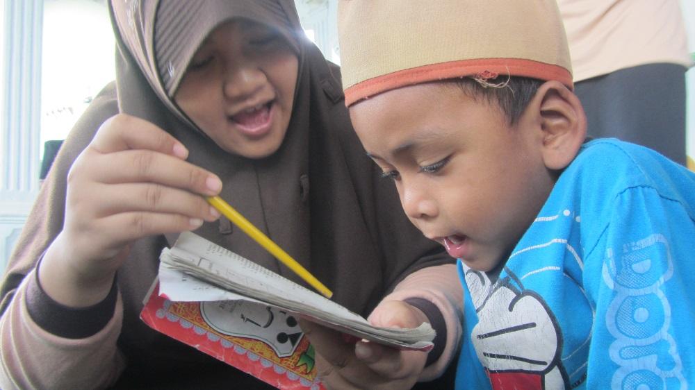 (foto: Sumayyah Martono) Salah satu peserta SMD akhwat sedang menuntun anak TPQ mengaji AL Qur'an