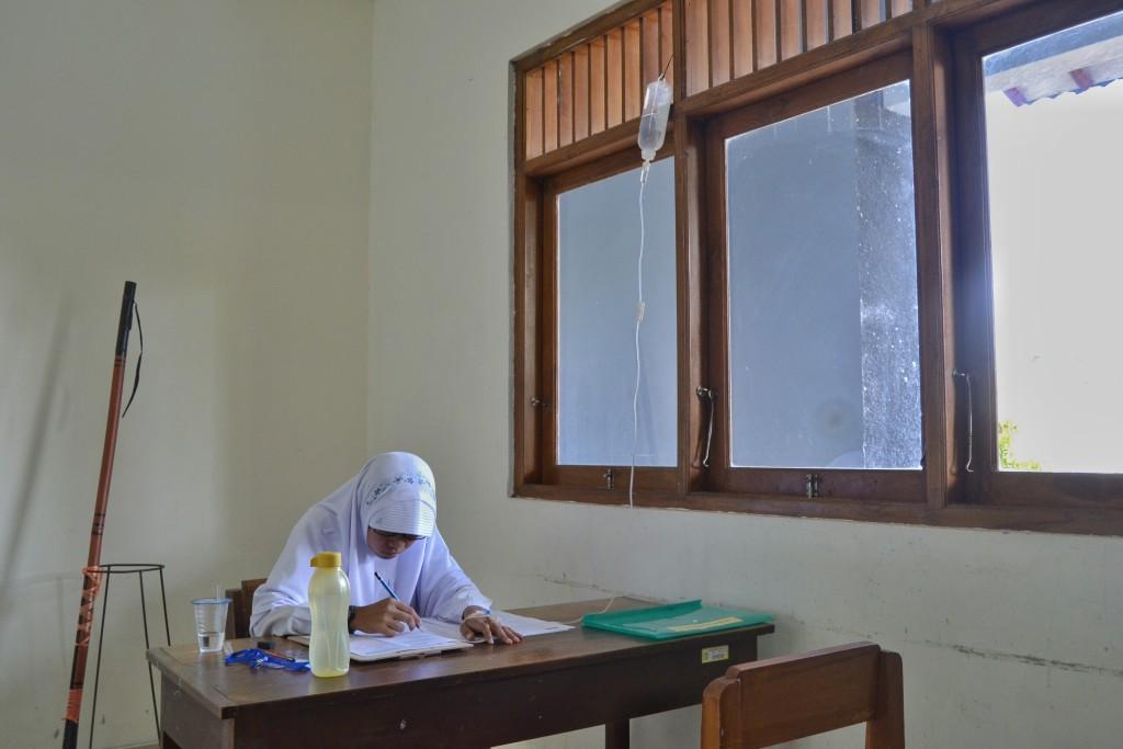 (Foto: Fu) Siswi SMAIT IF mengerjakan soal UN 2016 susulan dengan terpasang infus.